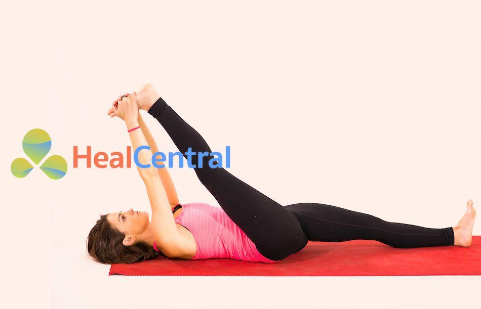 Tư thế yoga Supine Hand-To-Ankle Stretch cho người bị sưng đau khớp gối